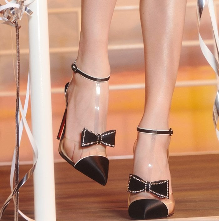Composed of black satin and clear PVC, these pumps are designed with a pointed toe
