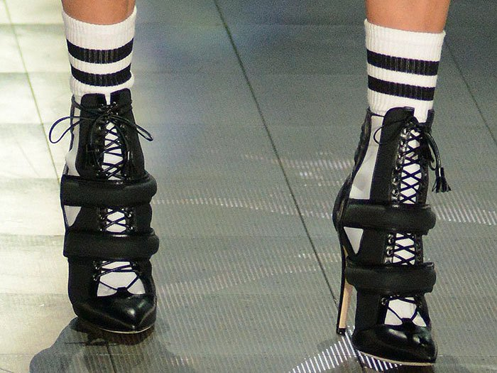 Closeup of Bella Hadid's classic striped socks and sporty black-and-white lace-up booties with two padded straps across the front