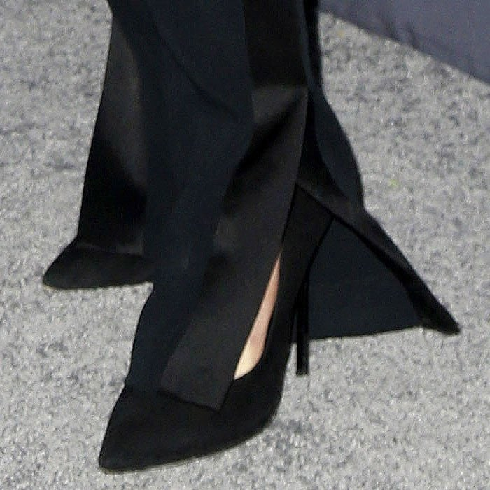 Cara Delevingne's Casadei black-suede blade-heel pumps peeking out from the slits on her tuxedo pants