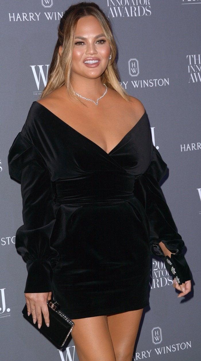 Chrissy Teigen ina blackoff-the-shoulder velvet mini dress fromAlexandre Vauthier