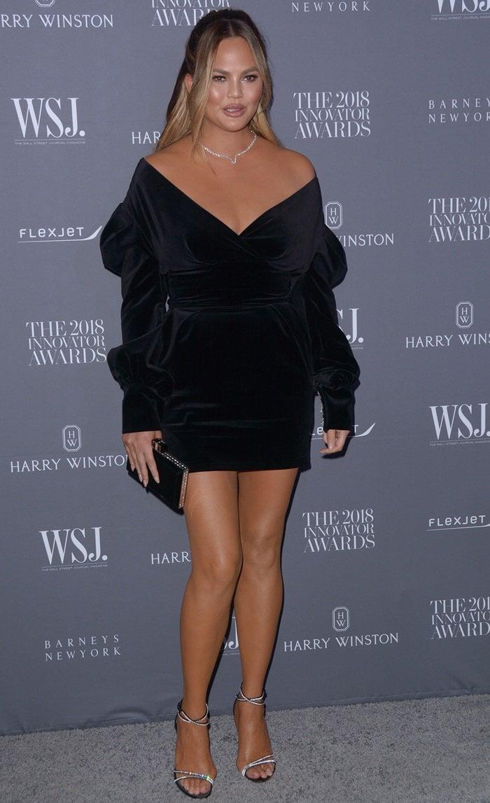 Chrissy Teigen flaunts her toned legs in a sumptuous black velvet mini dress
