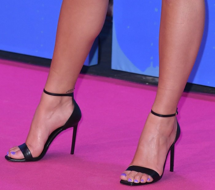 Dua Lipa put her sexy feet on display in black ankle-strap sandals