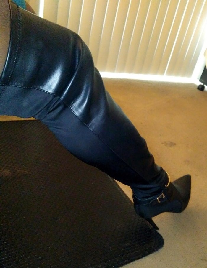 Sexy thigh-high boot featuring a stiletto heel, front faux-leather panel, stretchy neoprene back, and metal hardware accents