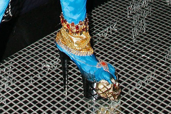 Details of Heidi Klum's blue platform boots featuring gold jewelry and long toenails clawing at a golden skull