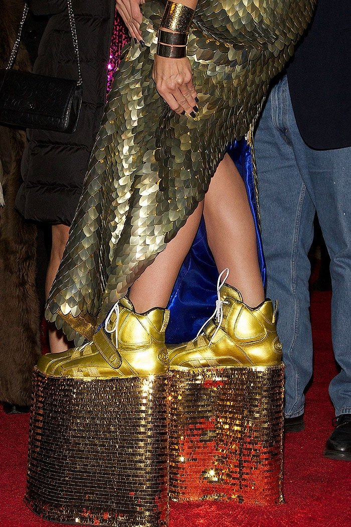 Heidi Klum showing off her sky-high, gold sequined platform sneakers