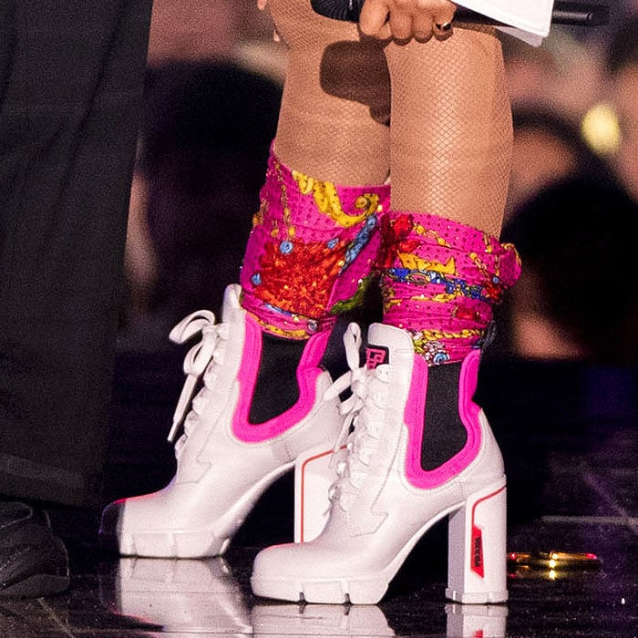 Details of Nicki Minaj's sporty white-leather Prada booties featuring chunky heels, lug-sole platforms, and neon-pink trim