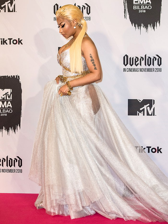 Nicki Minaj taking a step and showing a peek of her silver Jimmy Choo leg-tie sandals with double toe straps