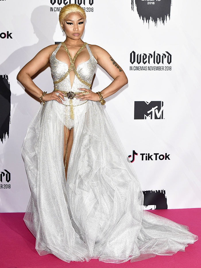 Nicki Minaj in a custom Versace Swarovski-crystal-encrusted mesh bodysuit and silver-tulle open-front ball skirt accessorized with a gold chain body harness, Medusa belt, and heavy chain-link bracelets