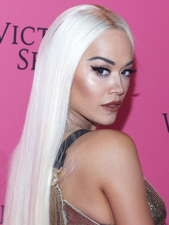 Rita Ora channeling Donatella Versace in a long, straight, platinum-blonde wig