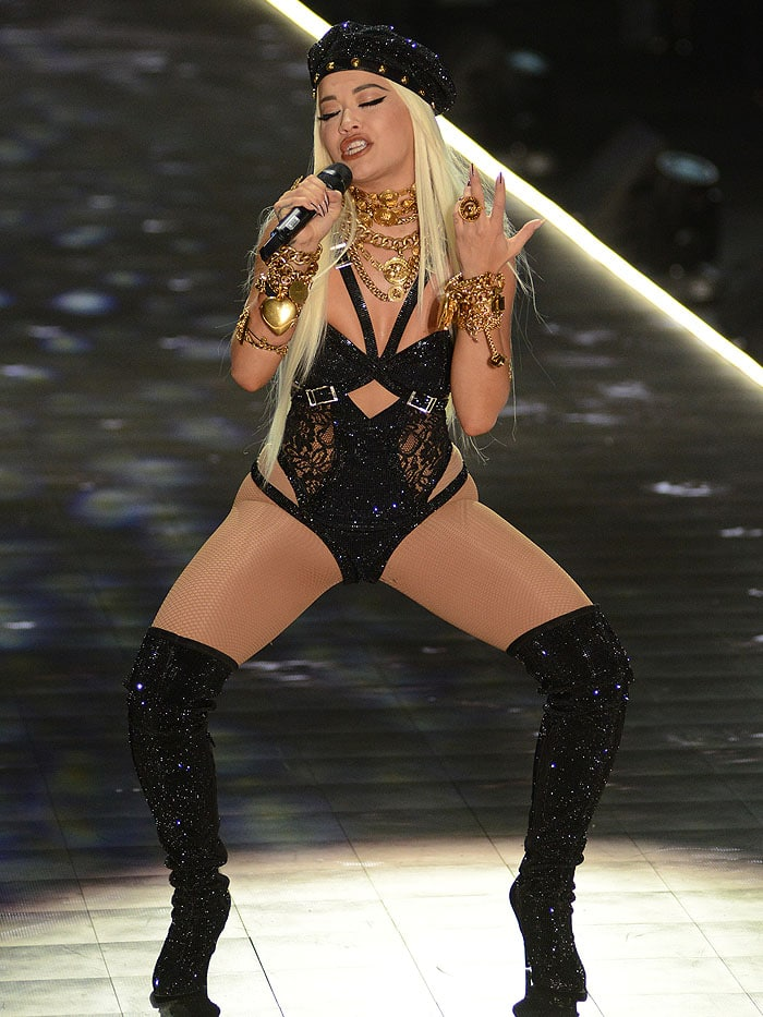 Rita Ora singing in a custom Versace look composed of a crystal-studded belted bodysuit, a crystal-and-gold-medallion-embellished beret, crystal-encrusted thigh-high boots, and heavy gold-chain jewelry