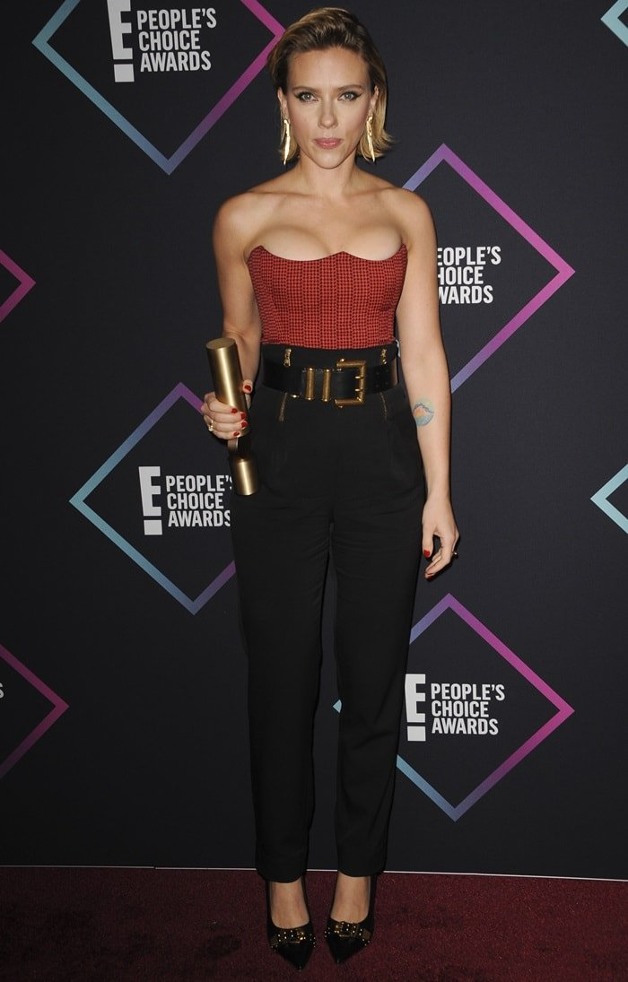 Scarlett Johansson wearing high-waisted slim leg pants with a printed cropped top from Versace