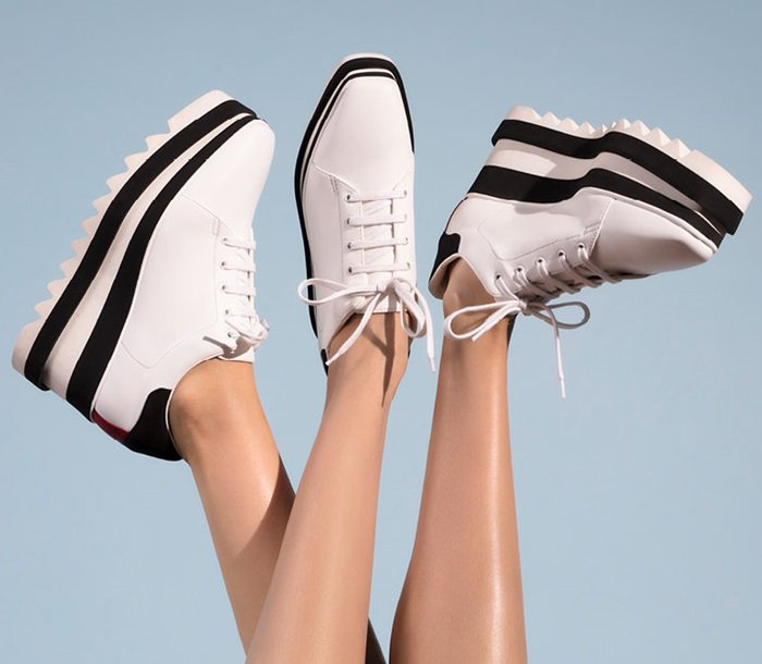 This sporty high heel tennis shoe goes modern with a chunky, striped platform and sawtooth-edged rubber sole