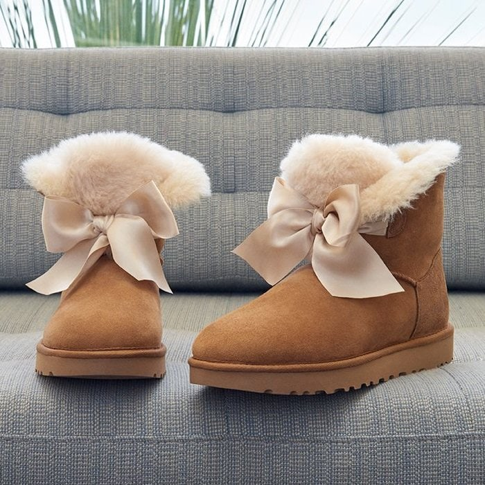 A tonal satin bow adds to the charm of a cozy boot lined and accented with genuine shearling