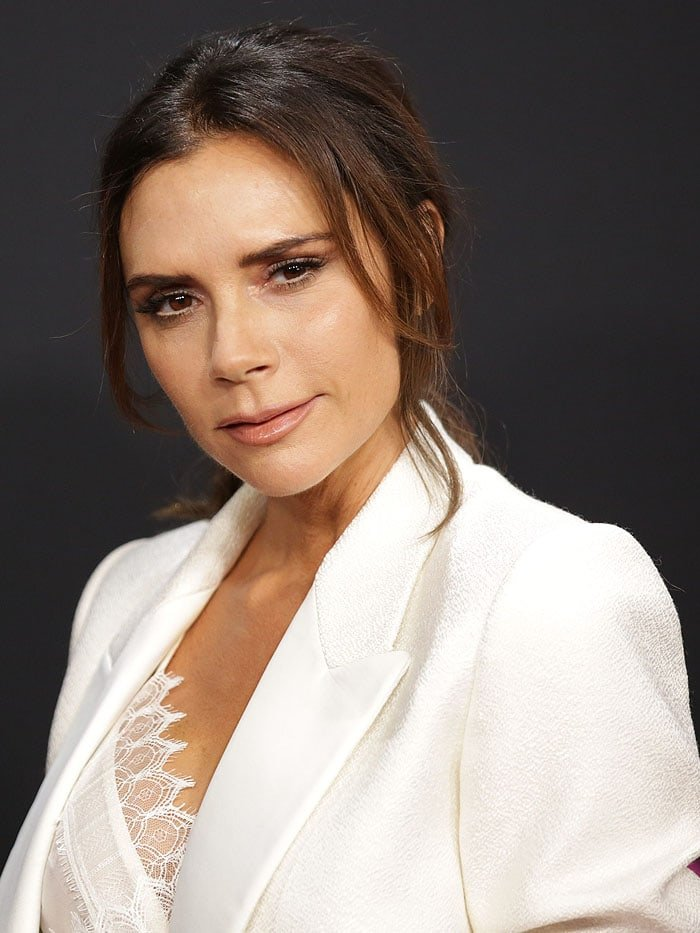 Victoria Beckham wearing a white lace-trim camisole and a tailored jacket from the Victoria Beckham Spring 2019 collection
