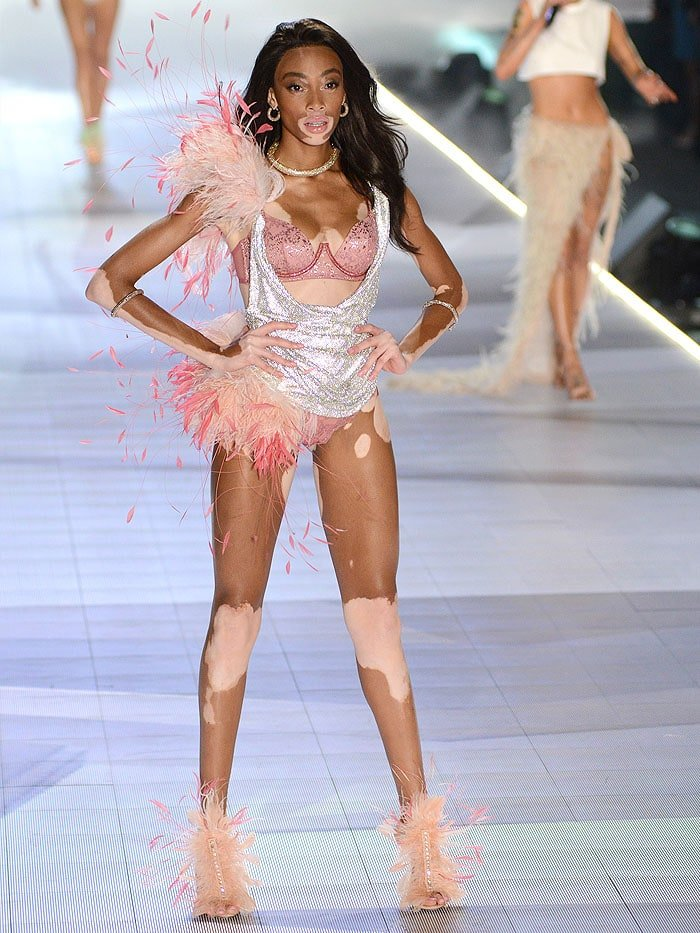Winnie Harlow floating down the runway in nude crystal-t-strap sandals embellished with beige and pink feathers