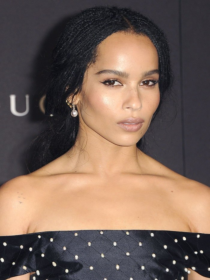 Zoe Kravitz complementing her look with pearl drop earrings and a bow made from the same pearl-embellished navy-satin fabric as her dress
