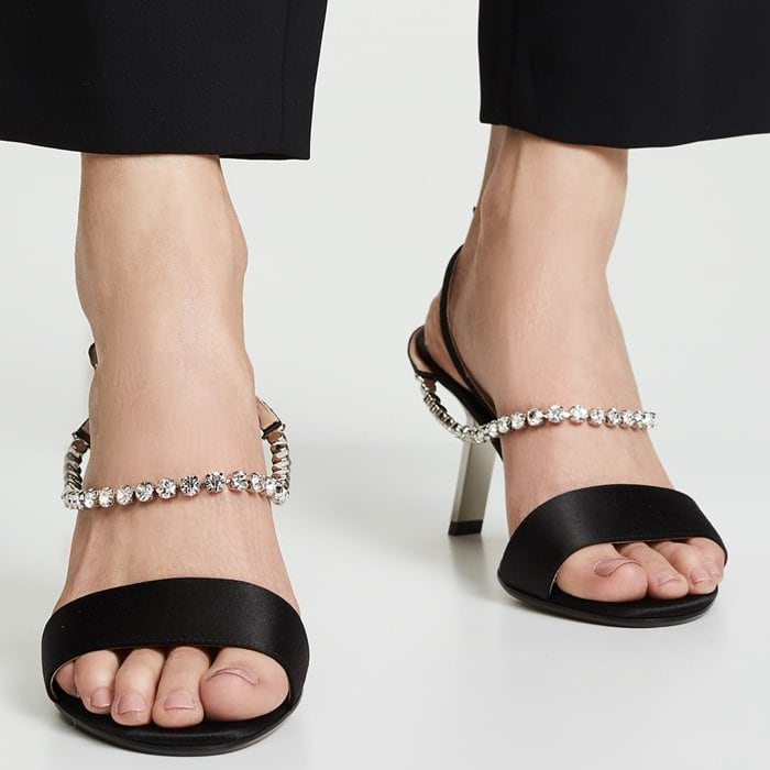 Crafted from silk satin and leather, these embellished sandals feature an open toe, two crystal embellished straps with an adjustable buckle fastening, a high stiletto heel that looks broken, and a leather sole