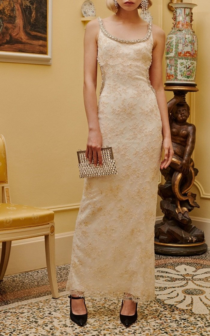 This lace dress features embellished detailing along the scoop neckline and a fitted column silhouette with an open back