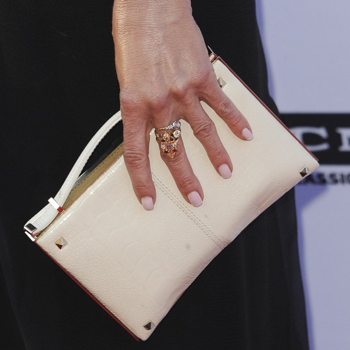 Jennifer Aniston toted a white Valentino clutch and accessorized withFred Leighton jewelry