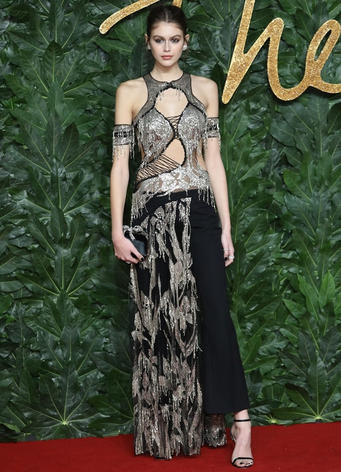 Kaia Gerber in a slashed silk tulle dress from the Alexander McQueen Spring 2019 Collection with pale silver metal sequin iris embroidery and black wool-silk bumster pants
