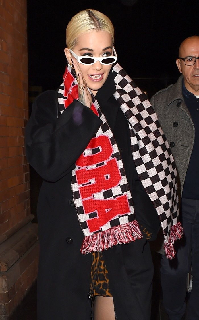Rita Ora wears a fringed checkerboard scarf that says 'HOUSE OF FUCKING HOLLAND'