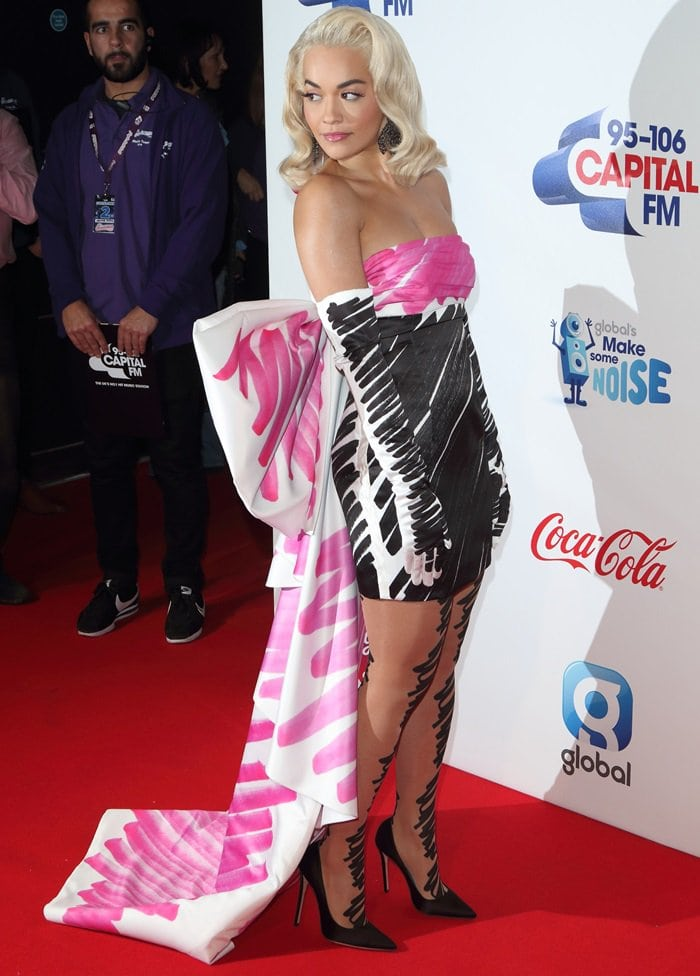 Rita Ora flaunts her sexy legs in a strapless satin dress from Moschino featuring a gigantic bow
