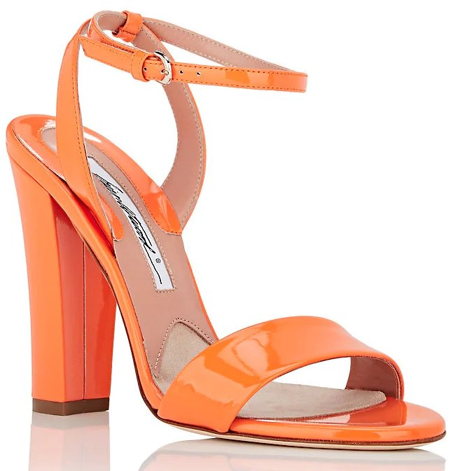 Styled with a leg-lengthening block heel, these ankle-wrap sandals are crafted in Italy of bright orange patent leather