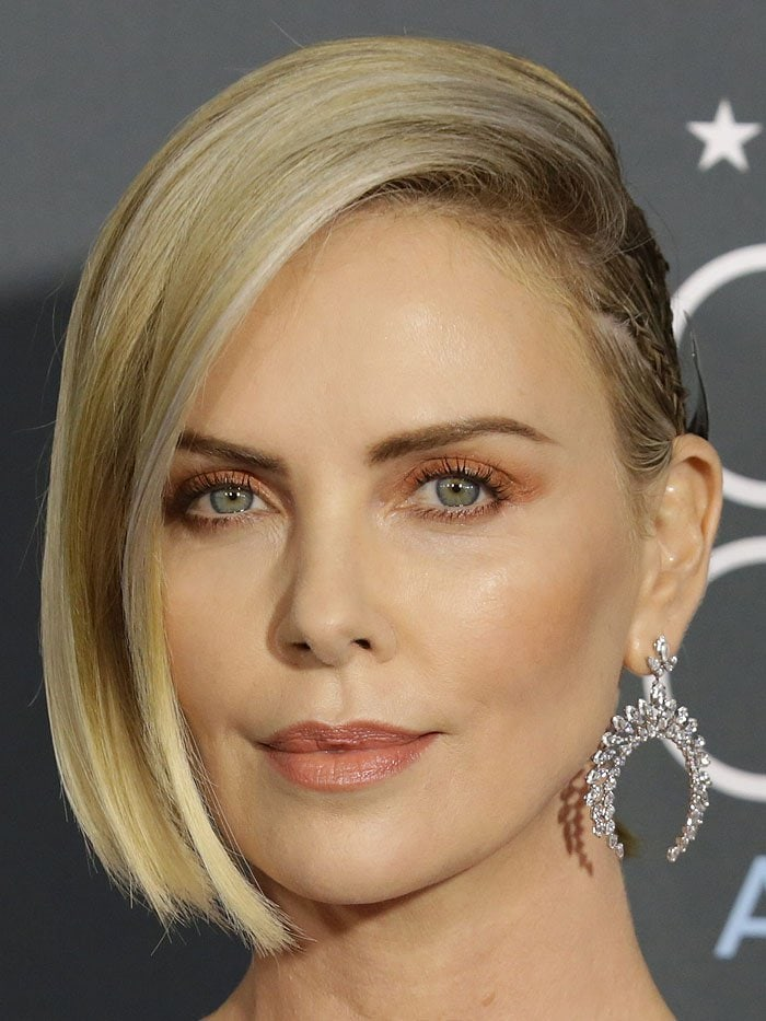 Charlize Theron wearing Messika 'Moonlight' high jewelry earrings and a custom Givenchy silver metal halo at the back of her half-slicked-back hairdo by Adir Abergel