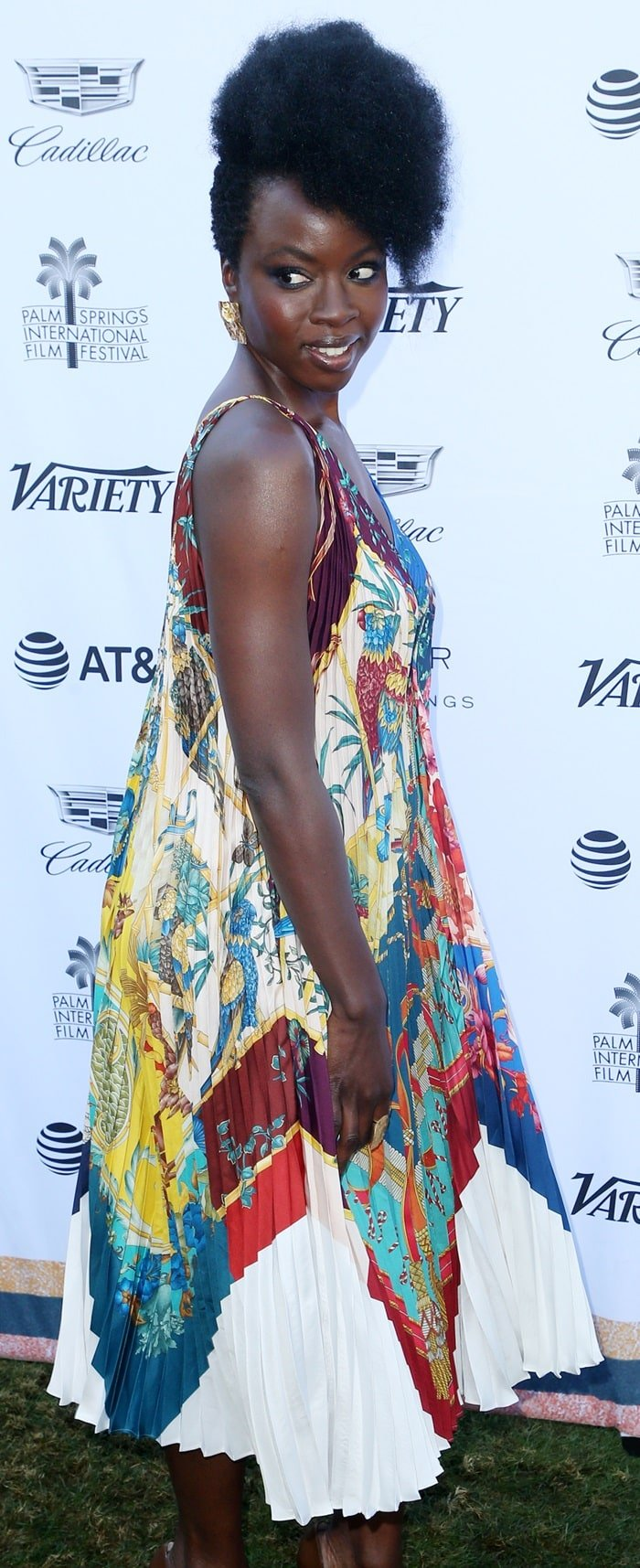 Danai Gurira flaunted her legs in a  printed pleated silk dress from Salvatore Ferragamo's Resort 2019 Collection