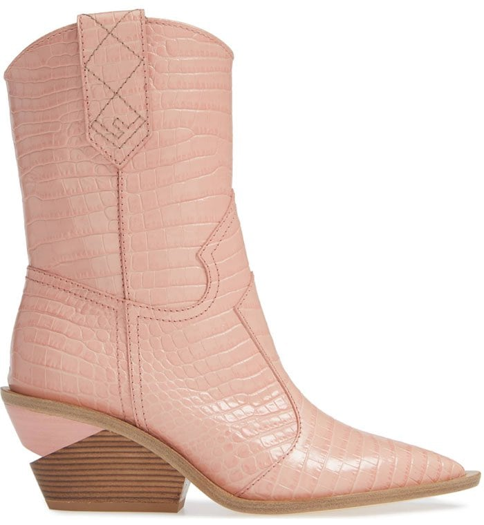 The pink of the millennium colors a section of a notched stacked heel and all of the glossy croc-embossed leather of updated Western boots with a sharp toe