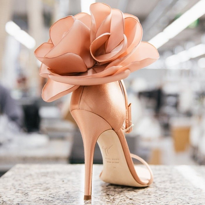 These nude pink leather peony appliqué sandals from Giuseppe Zanotti Design feature an open toe, an ankle strap with a side buckle fastening, a branded insole and a mid high stiletto heel