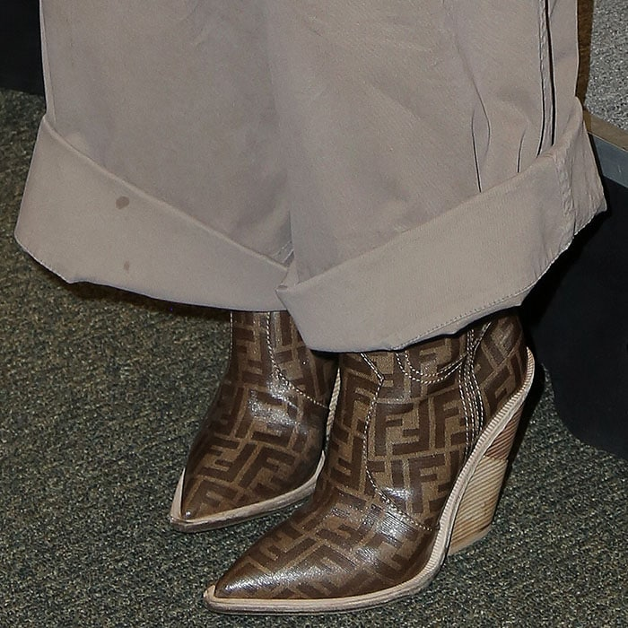 Closeup of Gwyneth Paltrow's Fendi logo-print cowboy boots and wide-leg khaki pants with stains on the rolled cuffs