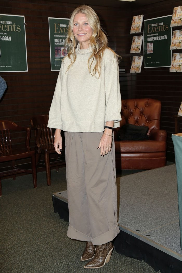 Gwyneth Paltrow in a frumpy brown outfit consisting of a loose beige turtleneck sweater, wide-leg pleat-front pants, and Fendi logo-print cowboy boots