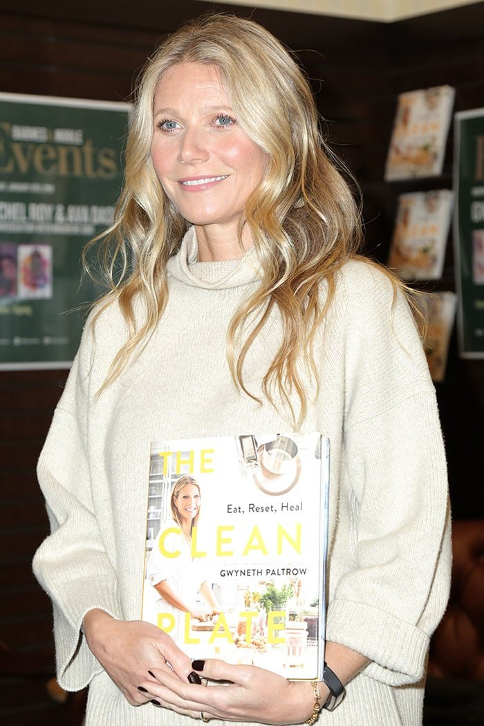 "Gwyneth Paltrow holding a copy of her latest book, ""The Clean Plate: Eat, Reset, Heal"""