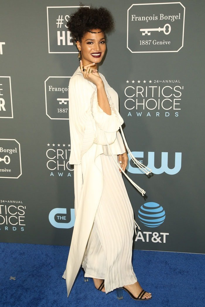 Indya Moore wearing a Louis Vuitton Resort 2019 white pleated long-sleeved gown and Louis Vuitton 'Silhouette' PVC-and-suede sandals