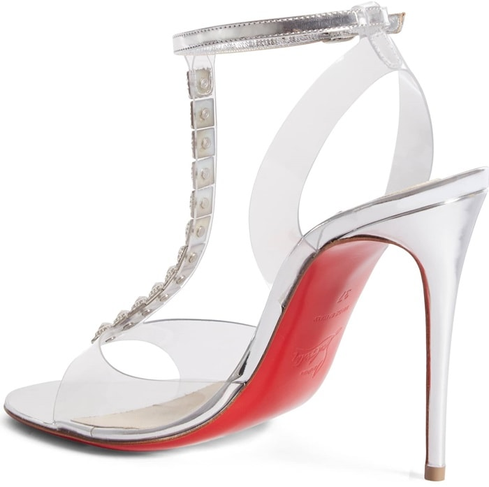 Sculpted pyramid studs ascend the T-strap of a towering sandal constructed with clear architecture and an iconic, nail-lacquer red sole