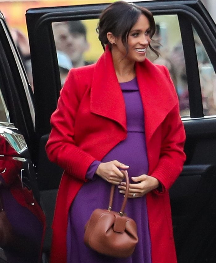 Meghan Markle revealed her due date in a Sentaler red coat paired with a purple Babaton by Artizia dress