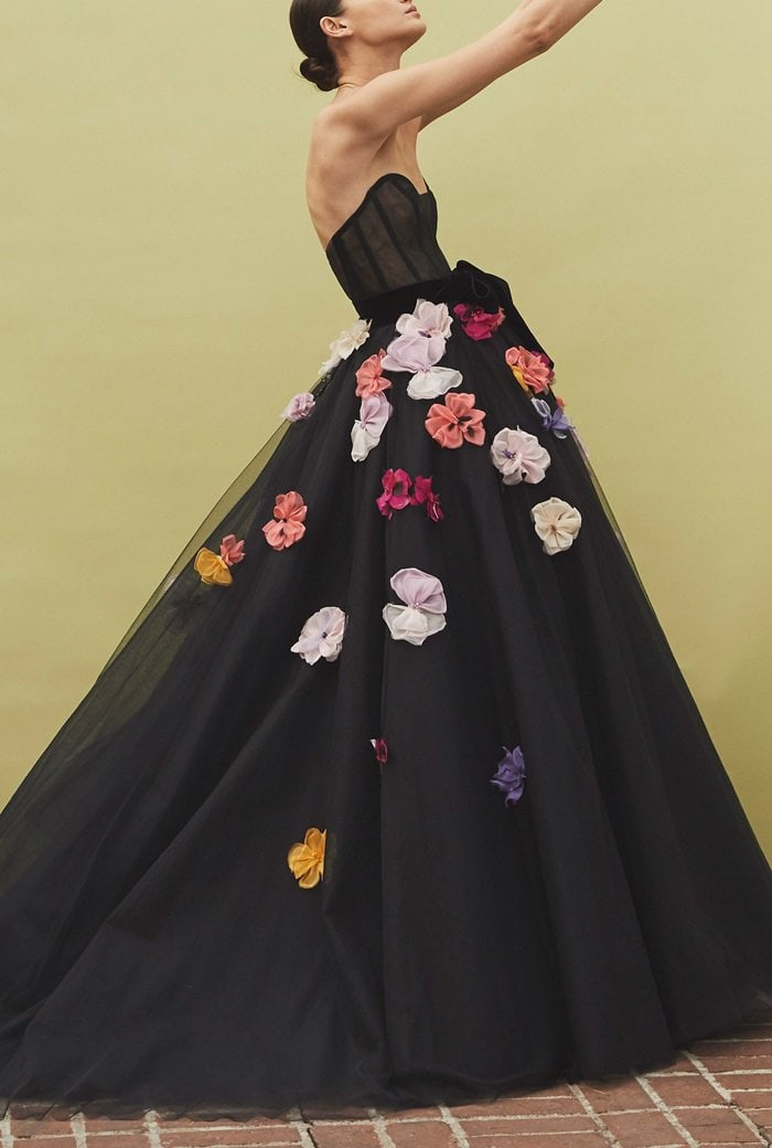 Monique Lhuillier's strapless dress is designed with a plunging sweetheart neckline, an A-line skirt, and 3-dimensional flower embellishments