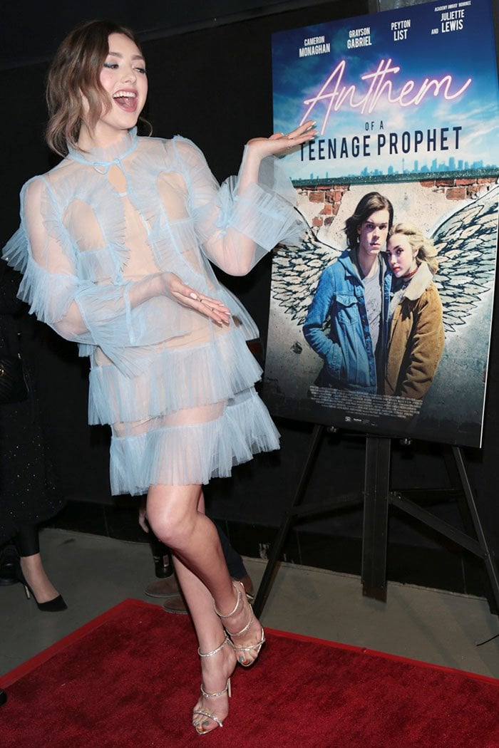 "Peyton List posing next to the ""Anthem Of A Teenage Prophet"" poster"