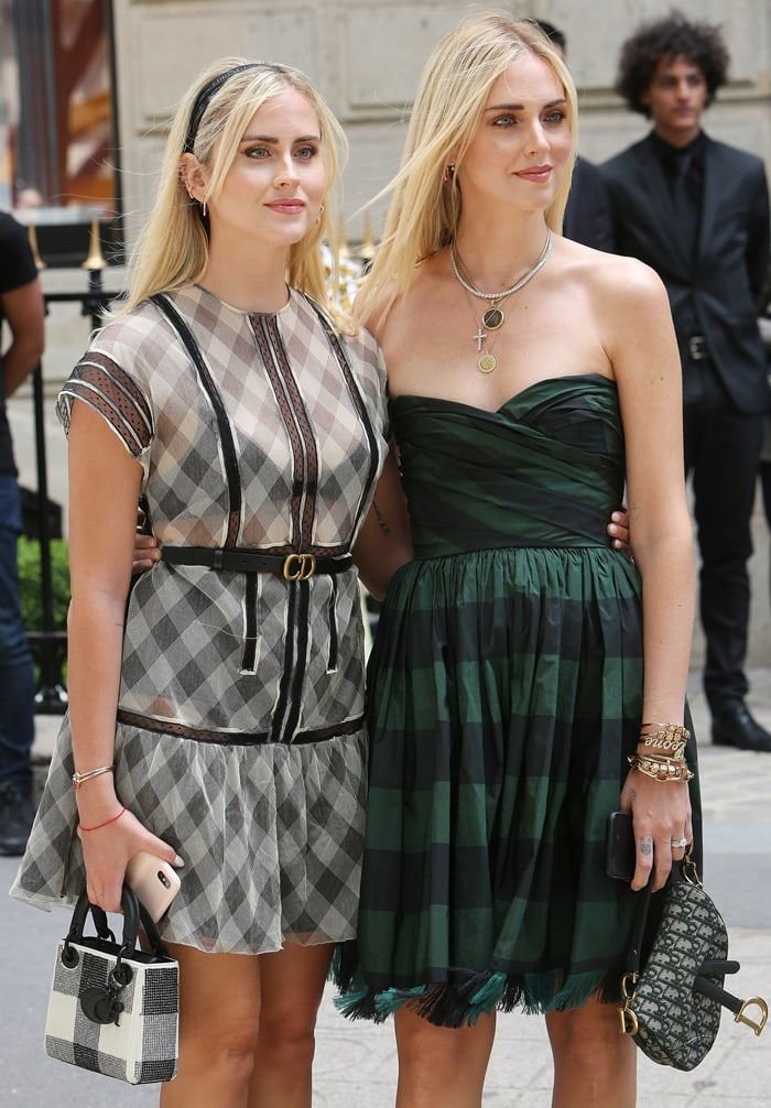 Valentina Ferragni (L), wearing a black and white checked dress and decorated Dior bag, and her sister Chiara Ferragni (R), wearing a green and black dress and black Dior bag, are seen outside Christian Dior show during Paris Fashion Week