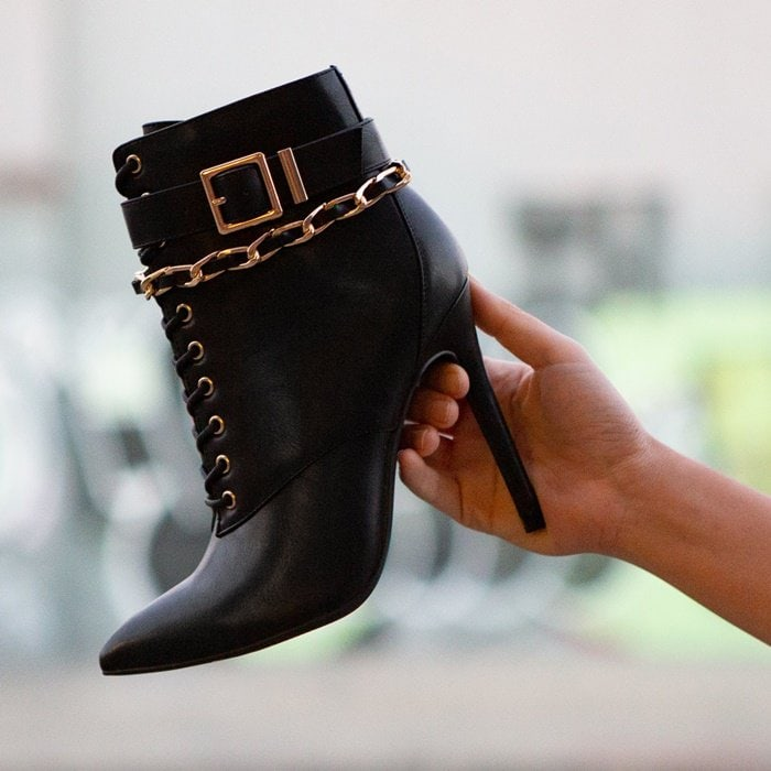 Lace-up bootie with a pointed toe, ankle chain accent, and stiletto heel
