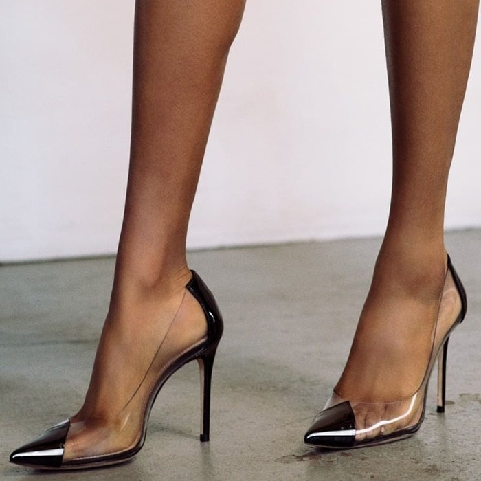 Transparent sides bring a charming glass-slipper aesthetic to a black pointed cap-toe pump lifted by a slender stiletto