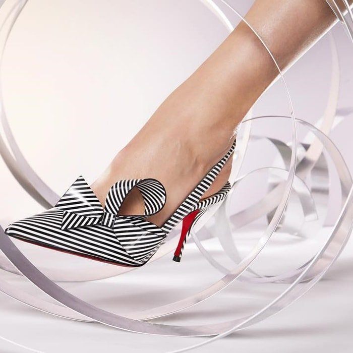 Its low-cut décolleté is adorned with a couture bow and reveals with modernity, the expertise of the Louboutin House