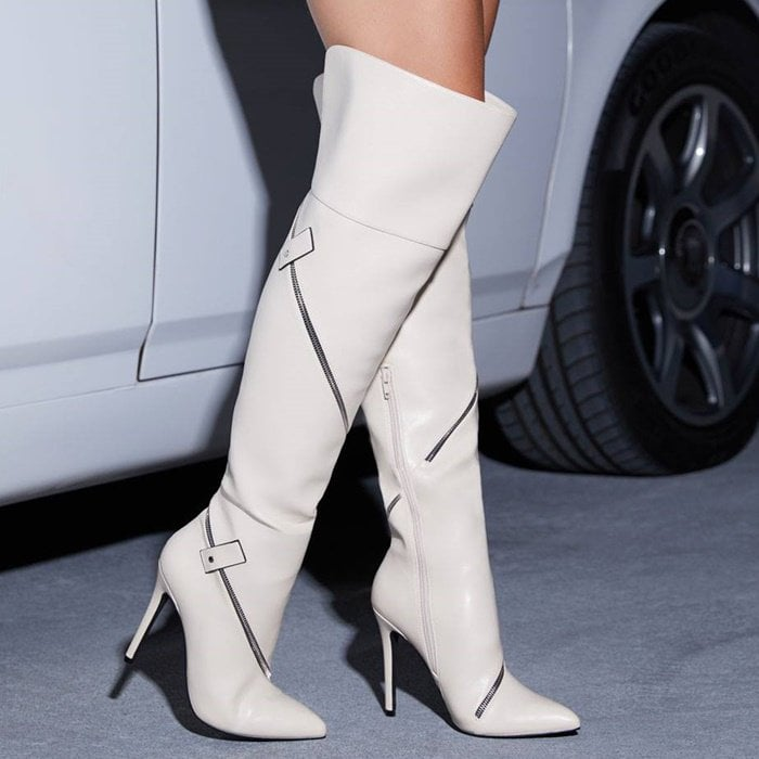 A thigh-high stiletto boot featuring non-functional wraparound zippers with straps