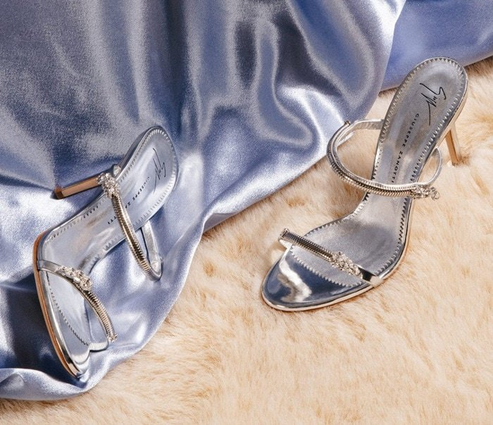 Made from silver shooting patent leather, these sandals are embellished with jewels on the straps