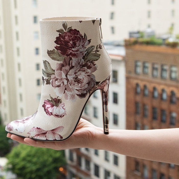 A classic stiletto floral ankle bootie with a pointed toe and back zipper closure.