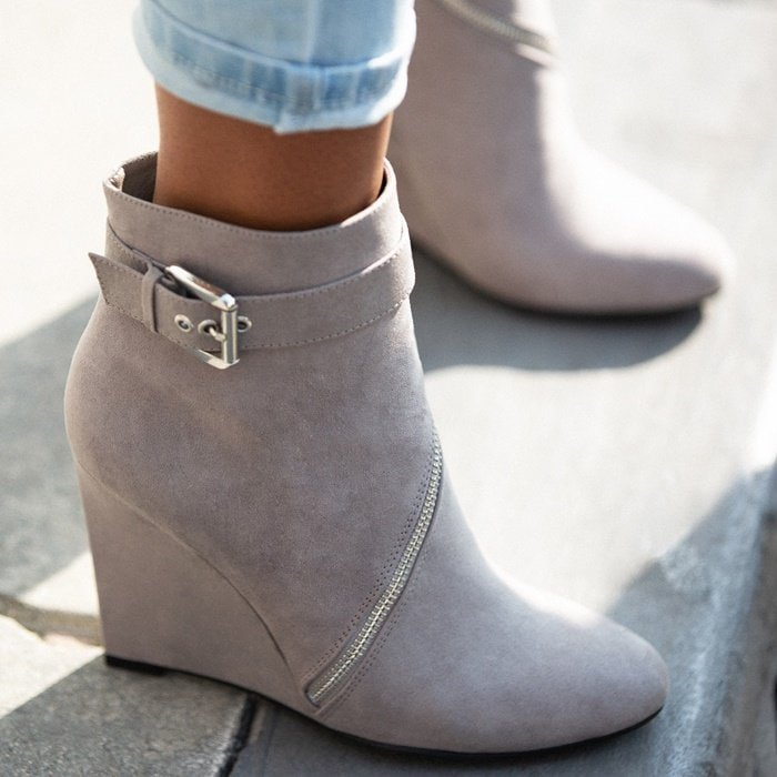 A single sole wedge bootie with non-functional wraparound zippers
