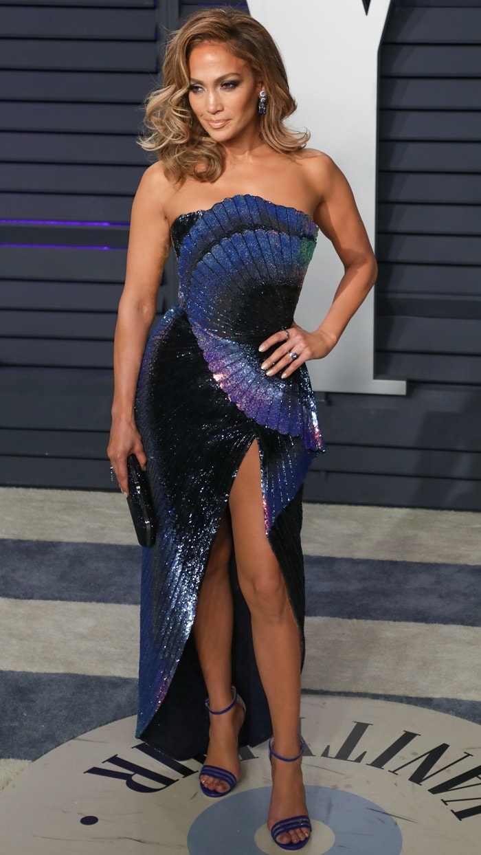 Jennifer Lopez flashed her legs in a midnight blue dress featuring shell pleats and coral reef fish prints