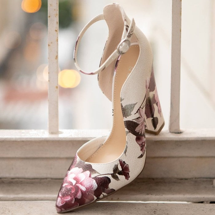 A pointed toe block heel pump with a curved topline and adjustable ankle strap buckle