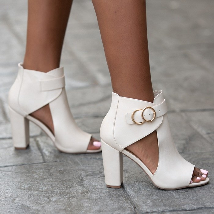 A cutout ankle bootie with a block heel, open toe,and double buckle detail